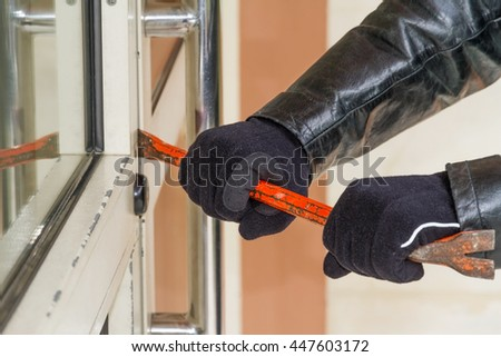 Burglar trying to break into a house with a crowbar