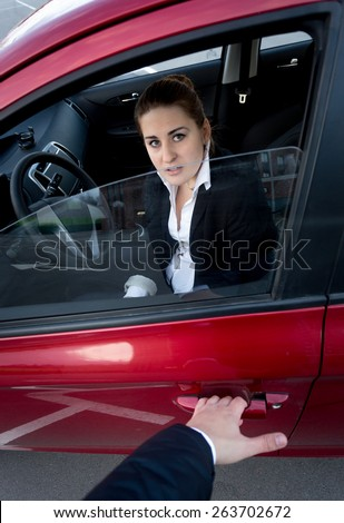 Burglar trying to break into the car. Scared woman blocking the door - stock photo