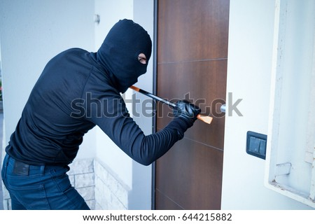 Burglar trying to force a door lock using a crowbar