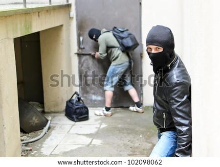 Burglary. One burglar tries open the door. Second is on the lookout - stock photo