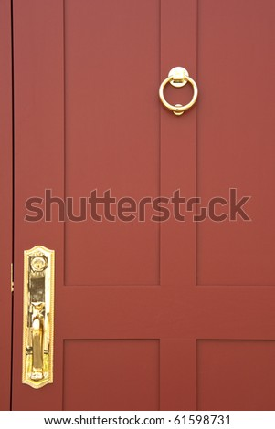 Burgundy colored door with brass handle and knocker - stock photo