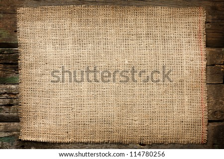 Burlap jute canvas vintage background on wooden boards - stock photo