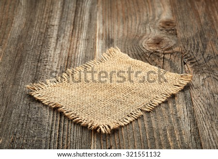 burlap napkin on old wooden table - stock photo