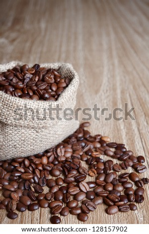 burlap sack of coffee beans on old wooden table.Shallow DOF - stock photo