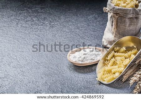 Burlap sack uncooked pasta kitchen scoop wooden spoon flour wheat rye ears on black background. - stock photo