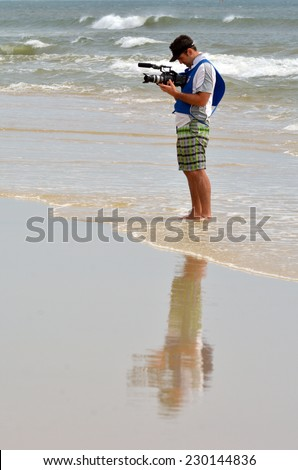 BURLEIGH HEADS, AUS - NOV 02 2014:Young Cameraman film on the beach.In 2006, there were approximately 27,000 television, video, and motion picture camera operators employed in the United States. - stock photo