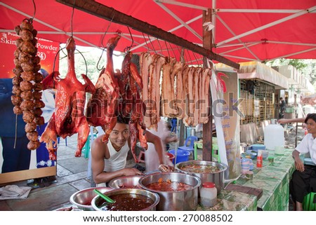 BURMA, RANGOON - FEBRUARY 12, 2011: Street local restaurant with hanging pork and pre-prepared rice & noodles for lunch. - stock photo