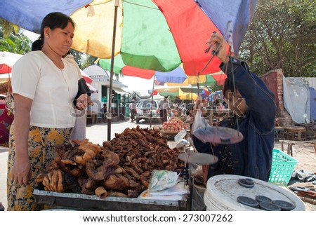 BURMA, RANGOON - FEBRUARY 13, 2011: Young boy is selling on street local market fried pork offals. - stock photo