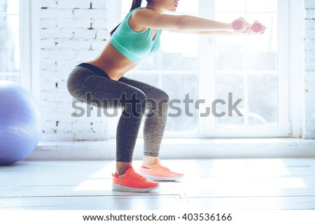 Burn in buttocks. Side view of young woman in sportswear doing squat and holding dumbbells while standing in front of window at gym - stock photo