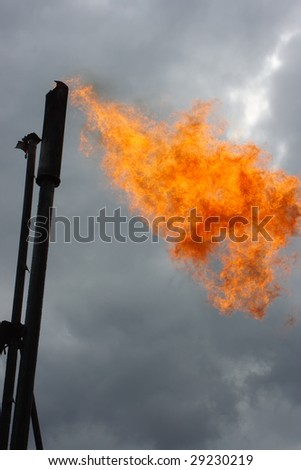 Burner flame of casing-head gas against a grey sky