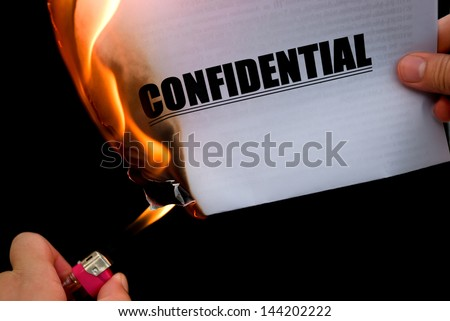 burning a confidential paper document - stock photo