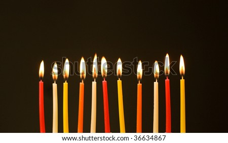 Burning birthday candles over the black background