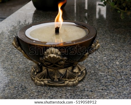 burning candel on tomb in cemetery