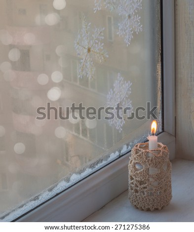 Burning candle a winter window, Christmas time. The eve of the first Advent - stock photo