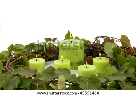 burning candle and ivy leaves on white