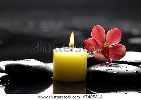 burning candle and pink orchid on zen stones/ tranquil spa scene - stock photo