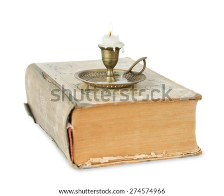 Burning candle in a brass candlestick stands on the old thick book isolated on white background - stock photo