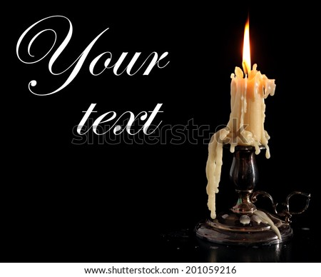 Burning Candle In Old Silver Candlestick Isolated on Black Background.  - stock photo