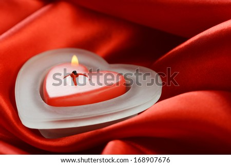 Burning candle in the form of heart on red silk - stock photo