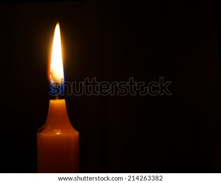 Burning candle on a black background. - stock photo