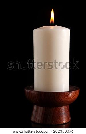 burning Candle on a Black Background. burning old candle vintage wooden candlestick. - stock photo