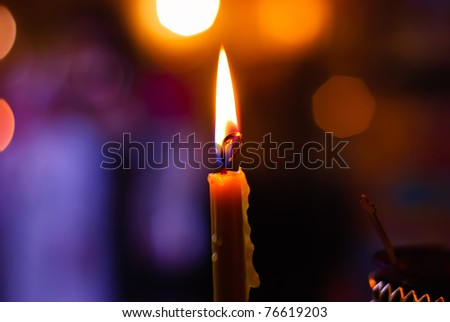 Burning candle on a blurred color background - stock photo