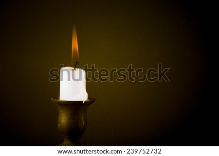 burning candle on a dark background. Tinted - stock photo