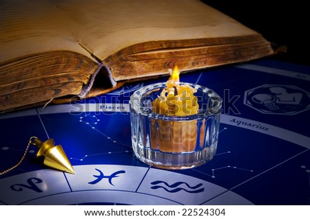 burning candle with a magic pendulum and old book on an astrological background - stock photo