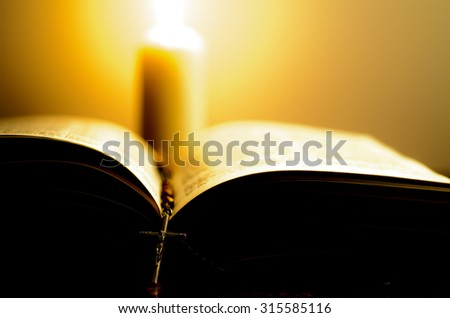 Burning candle with bright flame near the opened book with rosary. Shallow DOF. - stock photo