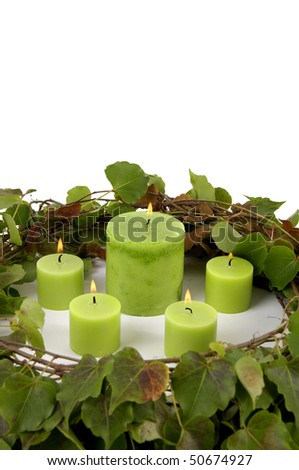 burning candle with circle green leaves