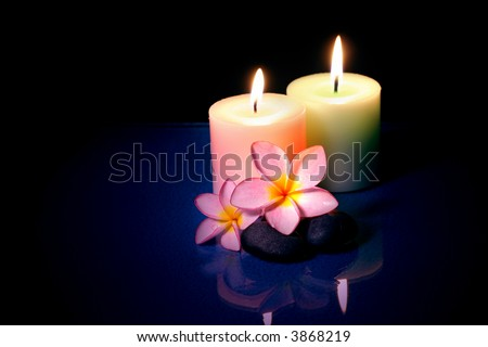 Burning candle with frangipane flowers in the night