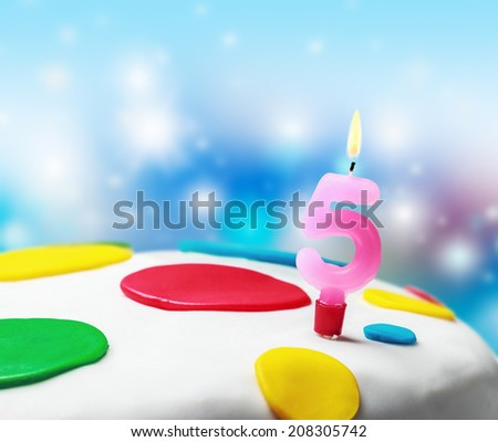 Burning candle with the number five on a birthday cake. birthday greetings  - stock photo