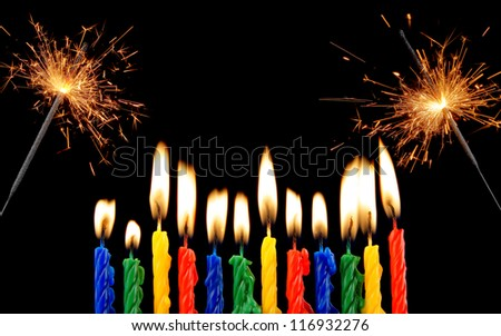 Burning candles and christmas sparklers on black background - stock photo