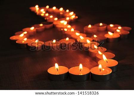 Burning candles as treble clef on dark background - stock photo