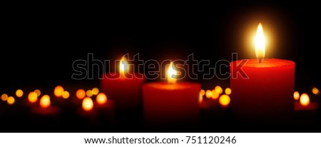 Burning candles gently glowing in the dark: tranquil low key shot with shallow depth of field for Christmas, spiritual and many more uses