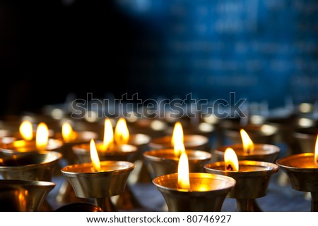Burning candles in sconces on black blue background - stock photo