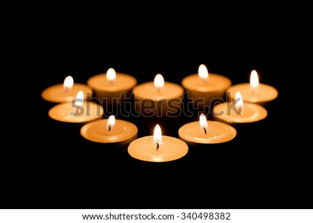 Burning candles in the form of heart on a black background - stock photo