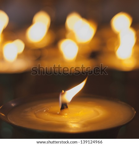 Burning candles in the monastery, India - stock photo
