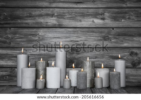 Burning candles in white and grey on wooden shabby chic background. Idea for a card for mourning, death or christmas. - stock photo