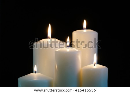 burning candles isolated on a black background. - stock photo