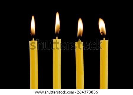 Burning candles isolated on black background - stock photo