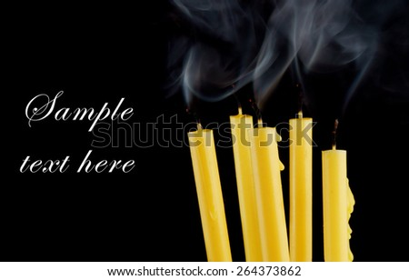 Burning candles isolated on black background with room for text - stock photo
