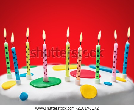 burning candles on a birthday cake on red background - stock photo