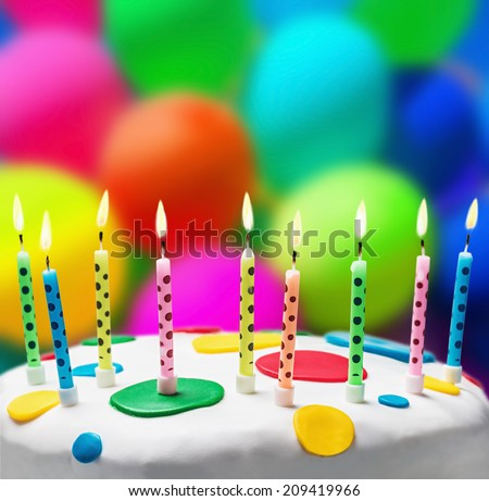 burning candles on a birthday cake on the background of balloons