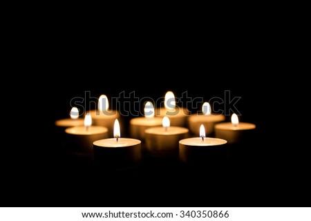 Burning candles on a black background - stock photo