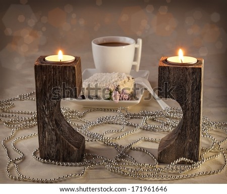 Burning candles on a candlestick in the form of heart and a cup of coffee - stock photo