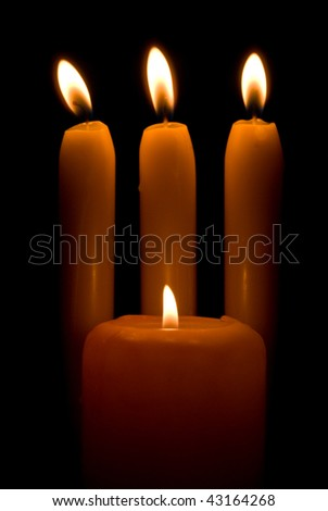 Burning candles over a black background