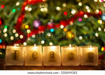 Burning candles spelling the word Peace in front of a lit decorated Christmas tree