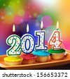 burning candles with the symbol of the new year on the cupcake   - stock photo
