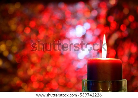 Burning Christmas candle against red bokeh background